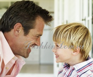 Young Man and a Young Boy (6-7) Looking at Each Other Laughing
